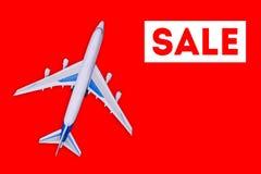 Lopp- och turismbegrepp Sale av flygbiljetter och loppkuponger Passagerarflygplan p? en r?d bakgrund arkivfoton
