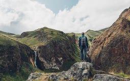 Loppaffärsföretagbegrepp Fotvandra mannen som överst står av den Cliff In Mountains And Enjoying sikten av naturen, bakre sikt arkivbild