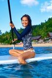 Loppaffärsföretag Kvinna som paddlar på surfingbräda Rekreation W Arkivfoto