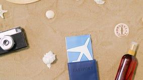 Loppbiljetter, kamera och hatt på strandsand arkivfilmer