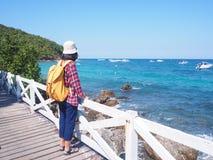 Loppet kvinnor som bär jeans och den röda plädskjortan och vandrar guling som gör att gå på bron, ser havet fotografering för bildbyråer
