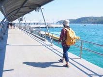 Loppet kvinnor som bär jeans och den röda plädskjortan och vandrar guling som gör att gå på bron, ser havet arkivbilder
