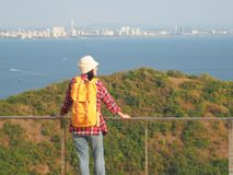 Loppet kvinnor som bär jeans och den röda plädskjortan och vandrar guling på synvinkeln på berget, ser havet royaltyfria foton