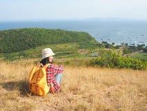 Loppet kvinnor som bär jeans och den röda plädskjortan och vandrar guling på synvinkeln på berget, ser havet fotografering för bildbyråer