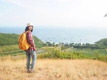 Loppet kvinnor som bär jeans och den röda plädskjortan och vandrar guling på synvinkeln på berget, ser havet royaltyfri foto