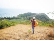 Loppet kvinnor som bär jeans och den röda plädskjortan och vandrar guling på synvinkeln på berget, ser havet arkivfoton