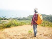 Loppet kvinnor som bär jeans och den röda plädskjortan och vandrar guling på synvinkeln på berget, ser havet arkivbilder