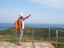 Loppet kvinnor som bär jeans och den röda plädskjortan och vandrar guling på synvinkeln på berget, ser havet arkivfoto