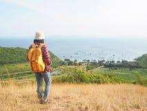Loppet kvinnor som bär jeans och den röda plädskjortan och vandrar guling på synvinkeln på berget, ser havet arkivbild