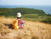 Loppet kvinnor som bär jeans och den röda plädskjortan och vandrar guling på synvinkeln på berget, ser havet royaltyfri bild