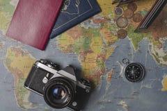 Loppet ställde in på världskartan Plånbok euro, kamera, pass, kompass royaltyfri foto