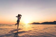 Loppkvinnor rymmer hatten och hopp på havsvågen fotografering för bildbyråer