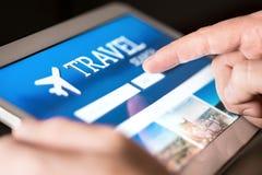 Loppsökandemotor och website för ferier Man som använder minnestavlan för att söka efter billiga flyg och hotell royaltyfri fotografi