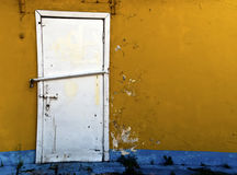 Lopsided Iron Door. A lopsided white iron door in a cracked wall Royalty Free Stock Image