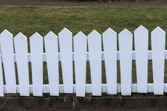 Lopsided white painted wood fence, grass in the back. Lopsided white painted wood fence with grass in the back Stock Photo