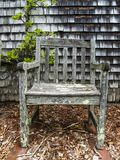 Lopsided old chair. Lopsided wooden chair flecked with lichen in public garden Stock Image