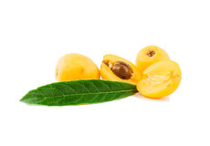 Loquat  fruit. Cut half-and-half with a stone and whole with leaves  on a white background Stock Photo