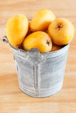 Loquat fruit in bucket. On wooden table. Selective focus Royalty Free Stock Images