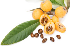 Loquat fruit (Eriobotrya japonica L.). Close up view of some loquat fruit and seeds  on a white Royalty Free Stock Image