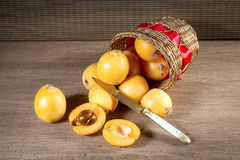 Loquats in basket on wooden background. Royalty Free Stock Photos