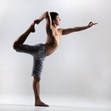 Lord of the Dance yoga pose. Sporty young man working out, yoga, pilates, fitness training, stretching exercise, asana Natarajasana, king dancer (Lord of the Royalty Free Stock Image