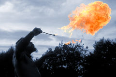 The Lord of the Flames. The fire breather and the orange flames Stock Image