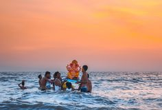 Lord Ganesha festival at water, Juhu Beach, Mumbai, India. Revelers in waves at Juhu Beach in Mumbai, India during Lord Ganesha Hindu festival at sunset Royalty Free Stock Photography