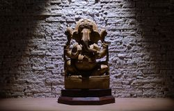 Lord Ganesha. ganesh statu on wooden table under direct light on beigh wall background stock photo