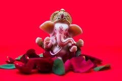 Lord Ganesha Idol com as pétalas cor-de-rosa no fundo vermelho, Ganesh Chaturth fotografia de stock