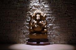 Lord Ganesha statu del ganesh sulla tavola di legno nell'ambito di luce diretta sul fondo della parete del beigh immagini stock libere da diritti