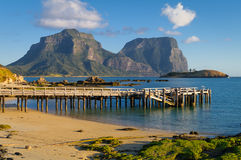 Lord Howe Island Lagoon and Jetty. Wooden jetty on Lord Howe Island Lagoon, Australia. The rugged peaks of Mt Lidgbird and Mt Gower are visible in the background Royalty Free Stock Photo