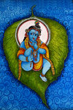 Lord Krishna som ligger på ett banyanblad Arkivfoto