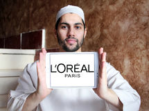 Loreal logo. Logo of beauty and cosmetics company loreal paris on samsung tablet holded by arab muslim man stock images