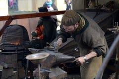 06 04 2015 Lorelay Tyskland - hovslagarearbetemetall med hammaren på städet i smedjan Royaltyfri Foto