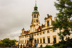 Loreta Facade. Exterior facade of Loreta church in Prague: green rooftop on white belfry, white walls, red rooftop. In a cloudy gloomy day, green trees park Royalty Free Stock Photography