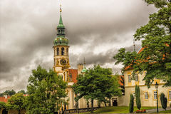 Loreta Facade. Exterior facade of Loreta church in Prague: green rooftop on white belfry, white walls, red rooftop. In a cloudy gloomy day, green trees park Royalty Free Stock Images