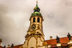 Loreta Facade. Exterior facade of Loreta church in Prague: green rooftop on white belfry, white walls, red rooftop. In a cloudy gloomy day, green trees park Stock Photography