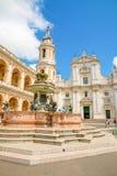 Loreto, Анкона, Италия - 8 05 2018: Квадрат Loreto с предпосылкой базилика в солнечном дне, портик к стороне Стоковые Изображения