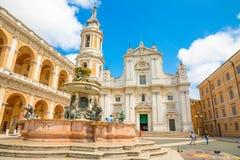 Loreto, Ancona, Italië - 8 05 2018: Vierkant van Loreto met achtergrond de basiliek in zonnige dag, portiek aan de kant stock afbeeldingen