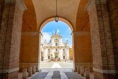 Loreto, Ancona, Italia - 8 05 2018: Quadrato di Loreto con fondo la basilica nel giorno soleggiato, portico al lato immagini stock libere da diritti