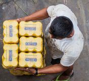 LORETO, PERU - JULY 15, 2015: Man holds a stack of beer cans of a peruvian brand Crist. Al stock image