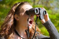 lornetki dziewczyna patrzeje scenę schocking Zdjęcia Stock