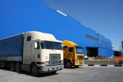 Lorries. On a background of a dark blue warehouse Stock Photography