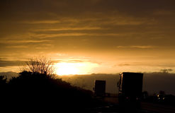 Lorries on a road at sunset Royalty Free Stock Images
