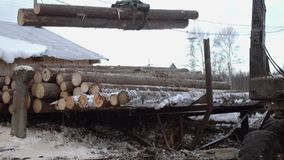 Lorry claw loader unloads wood logs from heavy truck at woodwork factory. Cold cloudy winter day stock video footage