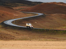 Lorry descending by windy road. Lorry descending brown hillside in Iceland by windy road Stock Photos