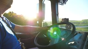 Lorry driver riding through countryside at sunset time. Man controlling his truck driving to destination. Close up stock footage