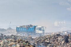 Lorry full of refuse at the garbage dump full of smoke, litter, plastic bottles,rubbish and trash at tropical island royalty free stock photo