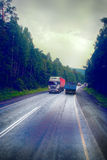 Lorry on highway-delivery of goods in bad weather threat. photo from the cab of a large truck on top Stock Photo