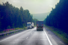 Lorry on highway-delivery of goods in bad weather threat. photo from the cab of a large truck on top Royalty Free Stock Photo